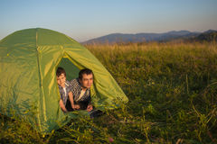Father and son look to the sunset from tent Royalty Free Stock Images