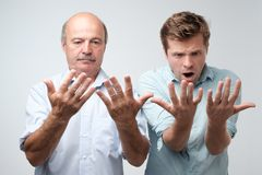 Father and son lookign at their palms with shock stock photography
