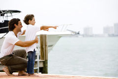 father and son looking across bay from dock Stock Photography