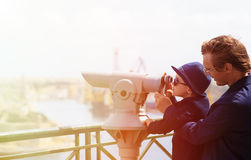 Father and son looking through binoculars at the Stock Images
