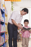 Father and Son Looking at a Book Together Stock Photography