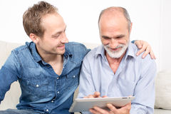 Father and son. Looking at device Royalty Free Stock Photos