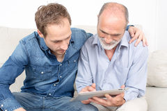 Father and son. Looking at device Stock Photos