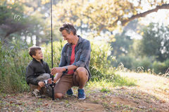 Father and son looking at each other while holding fishing rod. On field royalty free stock photo