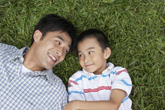 Father And Son Looking At Each Other While Lying On Grass. Smiling father and son looking at each other while lying on grass at park stock images