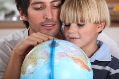 Father and son. Looking at globe stock photography