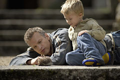 Father and son (3-5) looking at hedgehog beside steps, smiling Royalty Free Stock Photography
