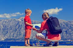 Father and son looking at map in mountains Royalty Free Stock Photos