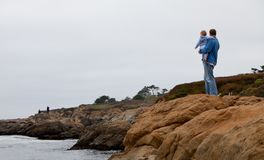 Father and son looking at the ocean Stock Photo