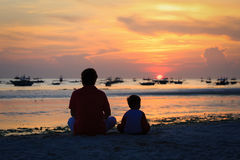 Father and son looking at sunset on beach. Father and son looking at sunset on tropical beach Royalty Free Stock Photo