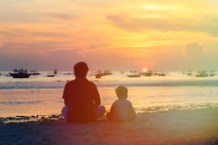 Father and son looking at sunset on beach Stock Images