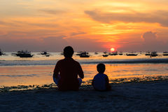 Father and son looking at sunset. On tropical beach Royalty Free Stock Photo