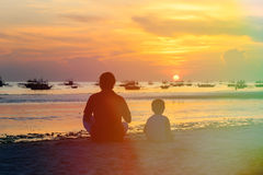 Father and son looking at sunset. On tropical beach Royalty Free Stock Photos