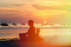 Father and son looking at sunset. On tropical beach Stock Image