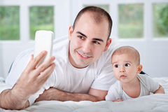 Father and son looking to phone and taking selfie Stock Photography
