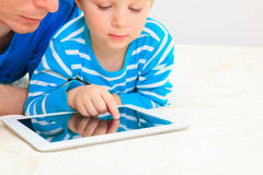 Father and son looking at touch pad Stock Image