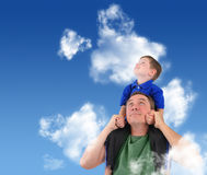 Father and Son Looking up in Cloud Sky. A father and son are looking up at the sky with clouds. The child is sitting on his dad's shoulders and looks happy stock photography