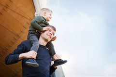 A father and son are looking up at the sky with clouds. The child is sitting on his dad's shoulders and looks happy Royalty Free Stock Photos