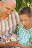 Father and son looking at wendy house. Father and son in early fall park. they looking at wendy house. focus on son's face. wendy house in out of focus Stock Images