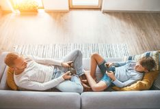Father and son Losted in electronic devices. They playing with tablet and gamepad sitting in living room royalty free stock image
