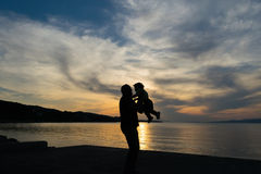 Father and son love silhouette against a dramatic sky. Royalty Free Stock Image