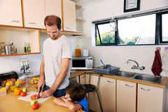 Father son lunch. Young boy watching father prepare healthy lunch Royalty Free Stock Photography