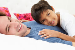 Father And Son Lying In Bed Together Stock Photography