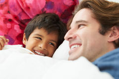 Father And Son Lying In Bed Together Royalty Free Stock Image