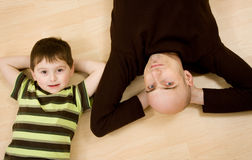Father and son lying down. A father and son lying down on the floor stock photography