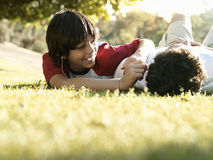 Father and son (10-12) lying on grass in park, smiling, surface level Stock Photography