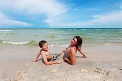 Father and son lying on the sandy beach. Stock Photos