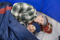 Father And Son Lying In Tent. Portrait of cheerful boy with father relaxing in camping tent Royalty Free Stock Images