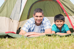Father and son lying beside their tent Stock Photography