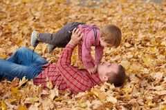 Father and son are lying on yellow leaves and having fun in autumn city park. They posing, smiling, playing. Bright yellow trees stock photos
