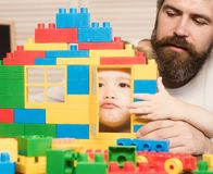 Father and son make grimaces looking through door of construction. Father and son make grimaces looking through door of toy construction. Kid hide behind house stock image