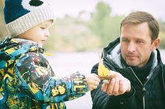 Father and son make and launch a boat made from autumn leaf, childhood, effect of instagram Stock Images