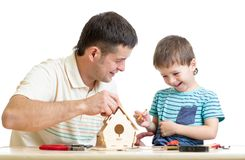 Father and son make nesting box together Stock Photo
