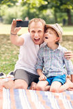 Father and son make a self photo in summer park Royalty Free Stock Image