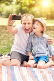Father and son make a self photo in summer park Stock Image