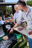 Father and son making barbecue and drinking beer while family sitting at table outdoors stock image
