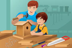 Father son making a birdhouse Stock Images