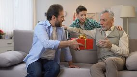 Father and son making birthday surprise for senior grandpa, giving gift box