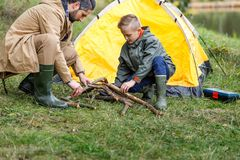 Father and son making bonfire. With sticks in camping with tent Royalty Free Stock Photos