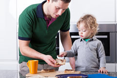 Father and son making breakfast together Stock Image