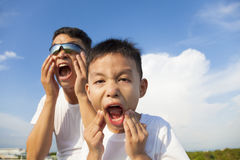 Father and son making a grimace together in the park Stock Photo