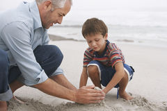 Father And Son Making Sand Castle On Beach Royalty Free Stock Photography