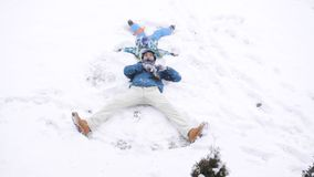 Father and son making snow angels stock video footage