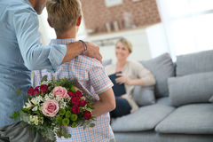Father with son making surprise for his mother. Son hiding bouquet to surprise mommy on mother's day Royalty Free Stock Photo