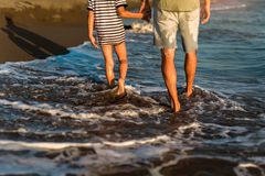 Father and son, man & boy child, running and having fun in the sand and waves. Of a sunny beach royalty free stock image