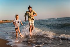 Father and son, man & boy child, running and having fun in the sand and waves of a sunny beach. Happy father and son, men & boy child, running and having fun in stock image